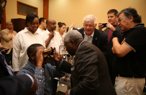 People look on as an eye care device use is demonstrated