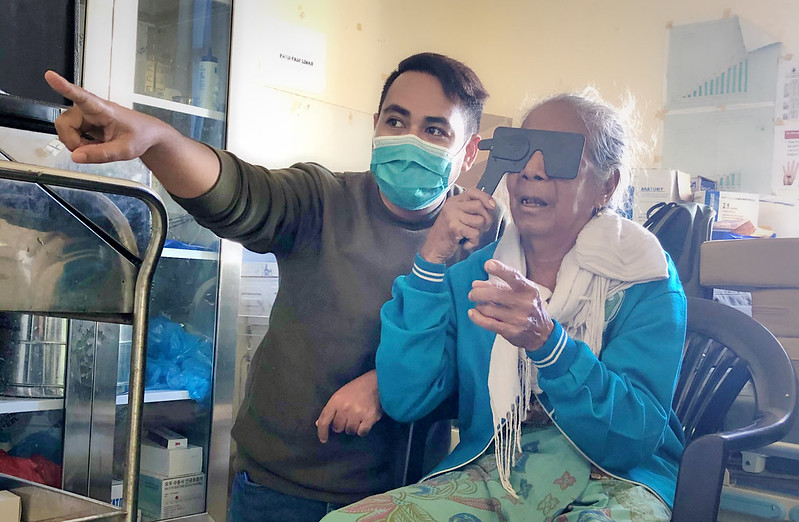 Man in mask providing a vision screening for an elderly woman