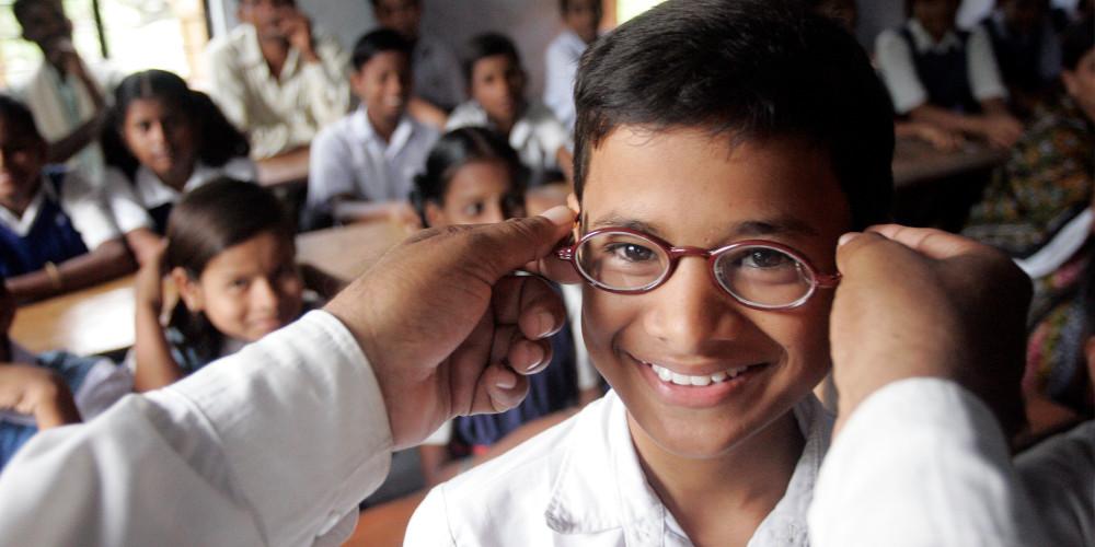 A man puts on a school boy's glasses