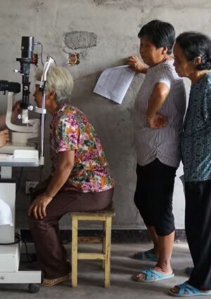 Diabetic retinopathy screening, with elderly women queueing to be examined at a slit lamp