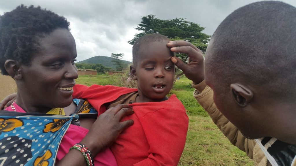 Photo credit: Ronald Kefa for the #StrongerTogether photo competition . A Trachomatous Trichiasis  (TT) Case finder examines a child's eyes in Kenya's Mara district.