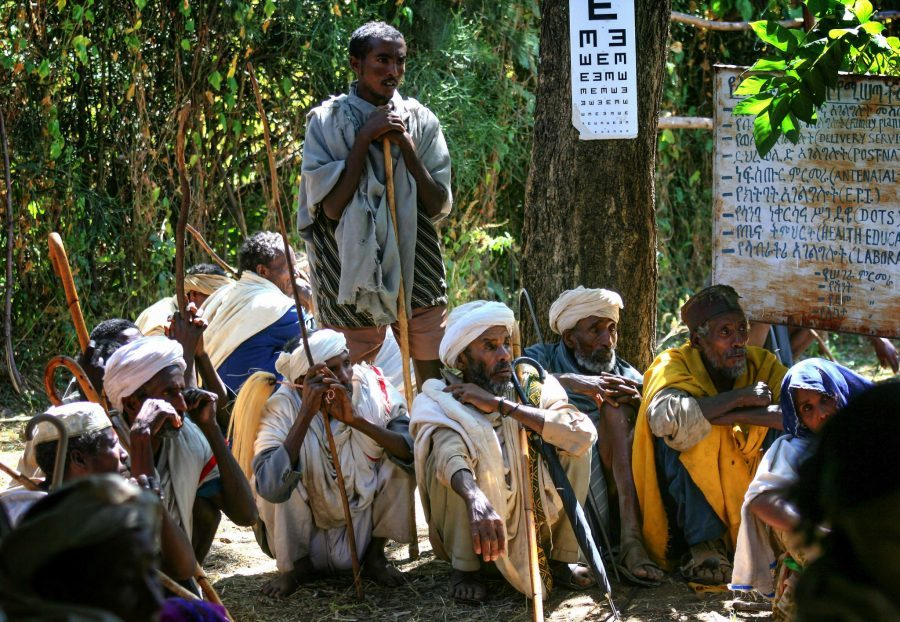 Farmers sitting under the shade of a tree a North Ethiopian rural health clinic waiting for eye tests