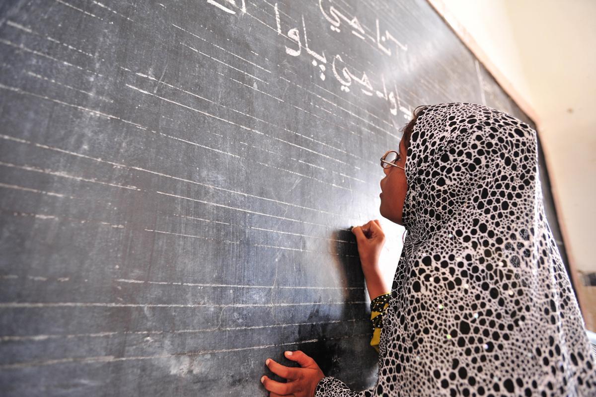 Child writing on the school blackboard