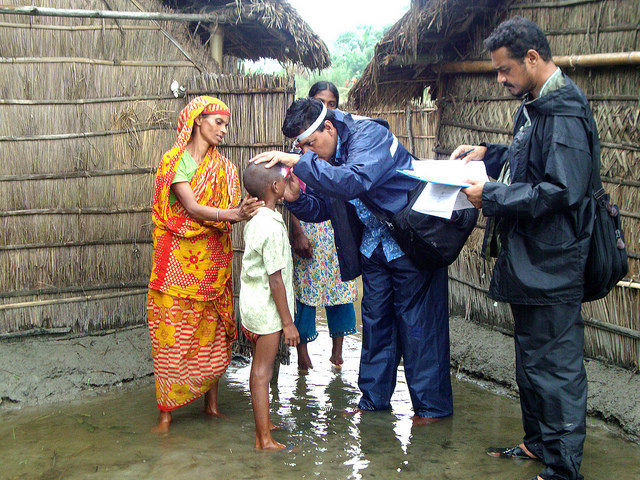 Eye test being conducted outside a straw hut in a water logged area in Bangladesh