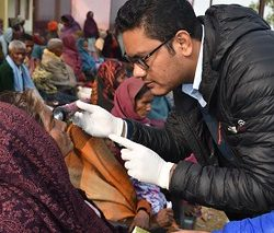 Ophthalmologist Examining eyes of Post Cataract Surgery patients from free surgical camp happened a day before --