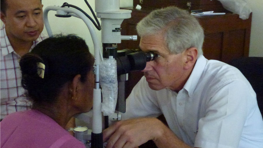 Story: Dr Cohn, recipient of AAO Humanitarian Service Award/ Image: Dr Cohn doing an eye exam