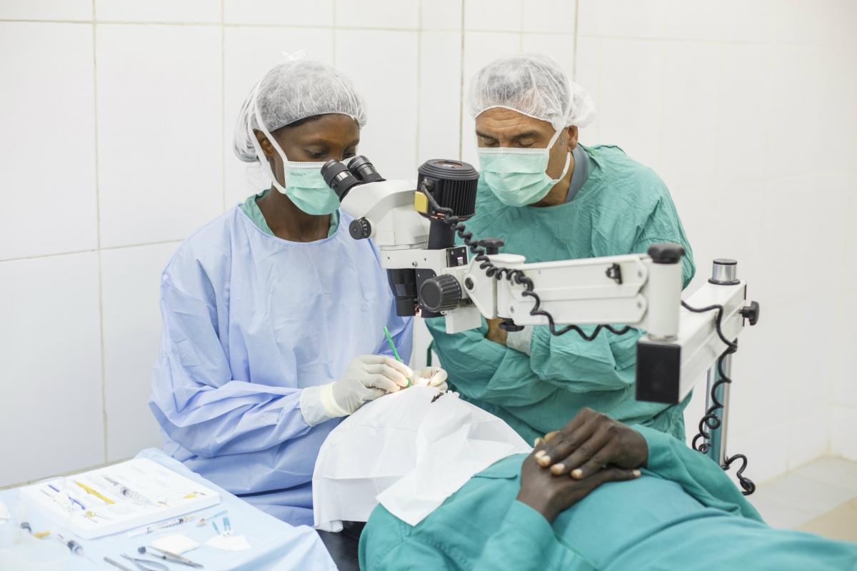 Dr Andre supervises a cataract surgeon in The Gambia