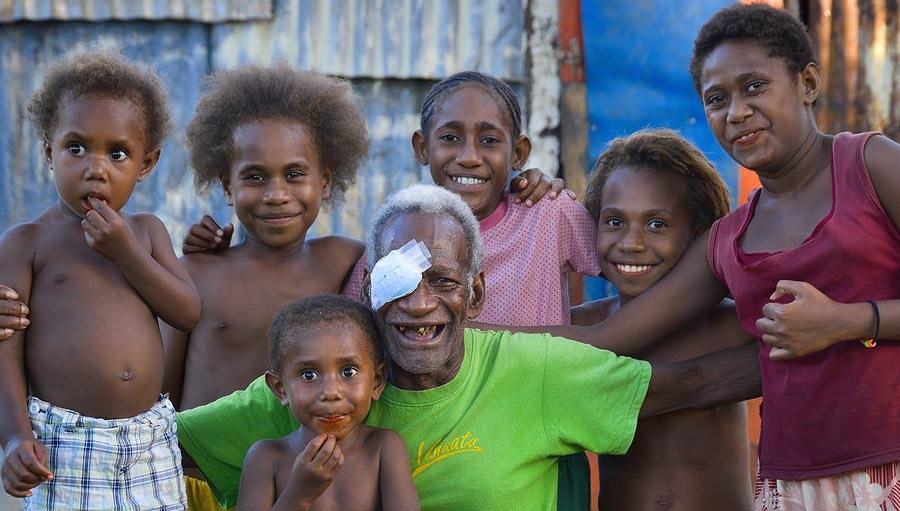Photo of an old man after cataract surgery with his family. Photo courtesy: Fred Hollows Foundation New Zealand