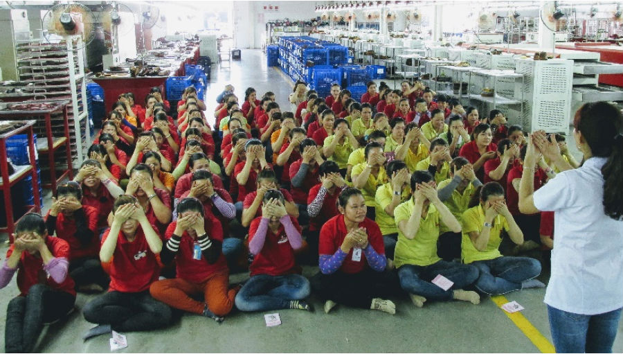 Factory workers learn about eye relaxation exercises.