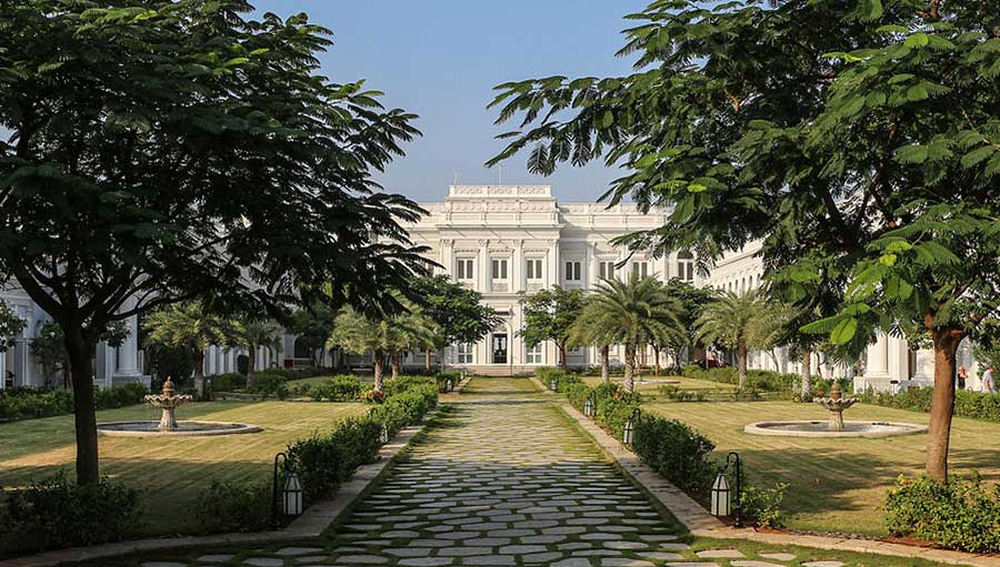 A pathway lined with trees leading to one of the sections of the Falaknuma Palace