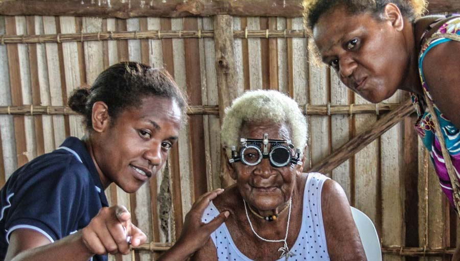 Explaining Vision Testing to an old woman during a Village Screening. FHFNZ, Papua New Guinea