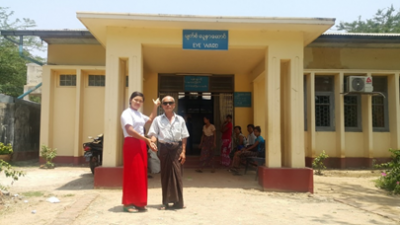 A midwife in Sagaing district, Myanmar, with a cataract patient outside a rural health facility