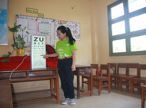 SCB staff member demonstrates reading an eye chart at Phu Tan Primary and Secondary School