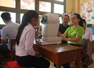 A Tien Giang hospital staff member demonstrates how to use the eye screening machine.