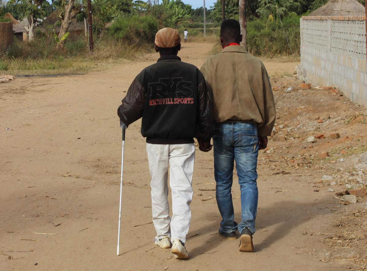 A blind man using a white cane, being assisted by another man