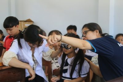 Standard Chartered Bank staff helping student in eye examination in Tien Giang