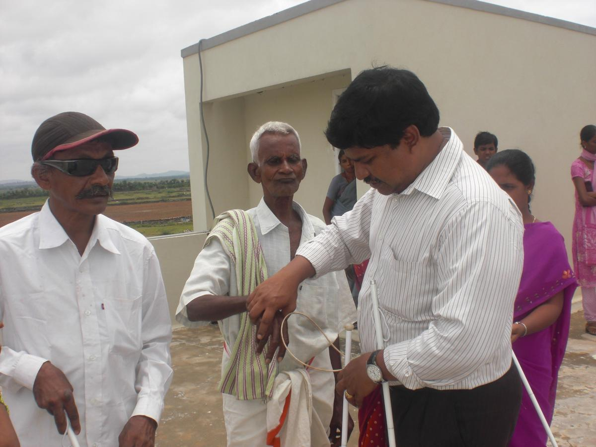 Sachin helping an elderly man use a white cane