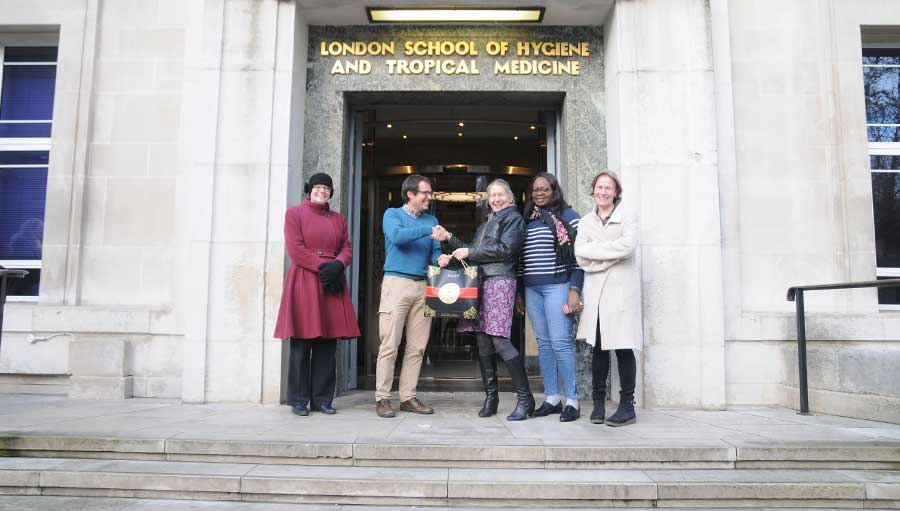 The winner is standing at the entrance of the London School of Hygiene and Tropical Medicine building with Sally Crook who is handing over a bag containing a DSLR camera. Three IAPB team members standing on each side are smiling at the camera