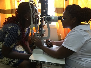 Ophthalmic nurse Rebecca Kissi tests a patient's vision at Tarkwa Municipal Hospital in Ghana, using a slit lamp that screens for diseases or abnormalities in the eye.