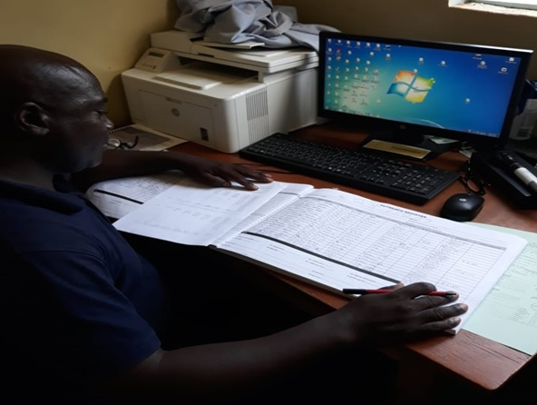 Mr Postan Phiri , Ophthalmic Nurse at Petauke Eye Clinic, aggregating data for monthly submission