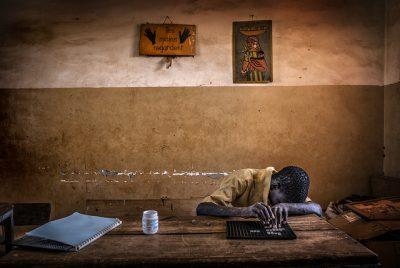 A blind boy does his homework