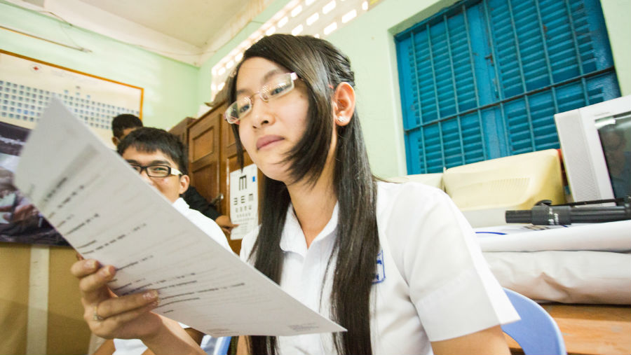 A female student with glasses reading from a paper