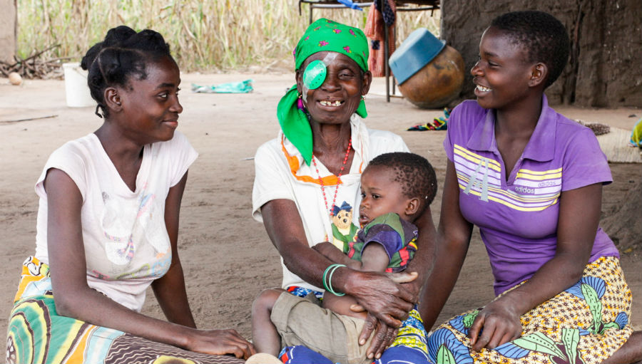 A woman from Mozambique sitting on the ground surrounded by two younger women, a child on her lap. She wears an eye patch over her right eye after cataract surgery.