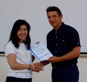 Thao, a participant, receiving a certificate from Karl Blanchett on completion of the course
