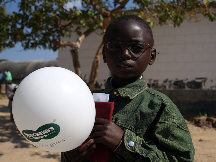 Image of a young boy with spectacles holding a specsaver balloon