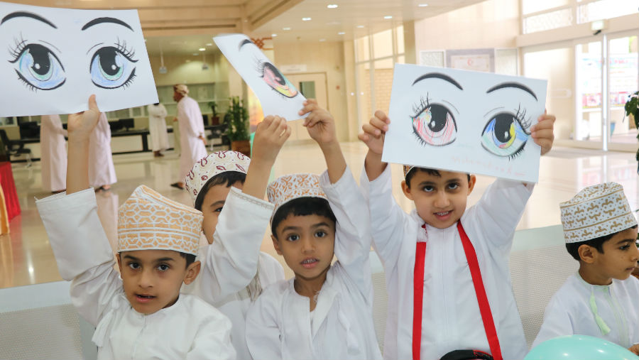 World Sight Day celebrations in Oman, children holding drawings of eyes