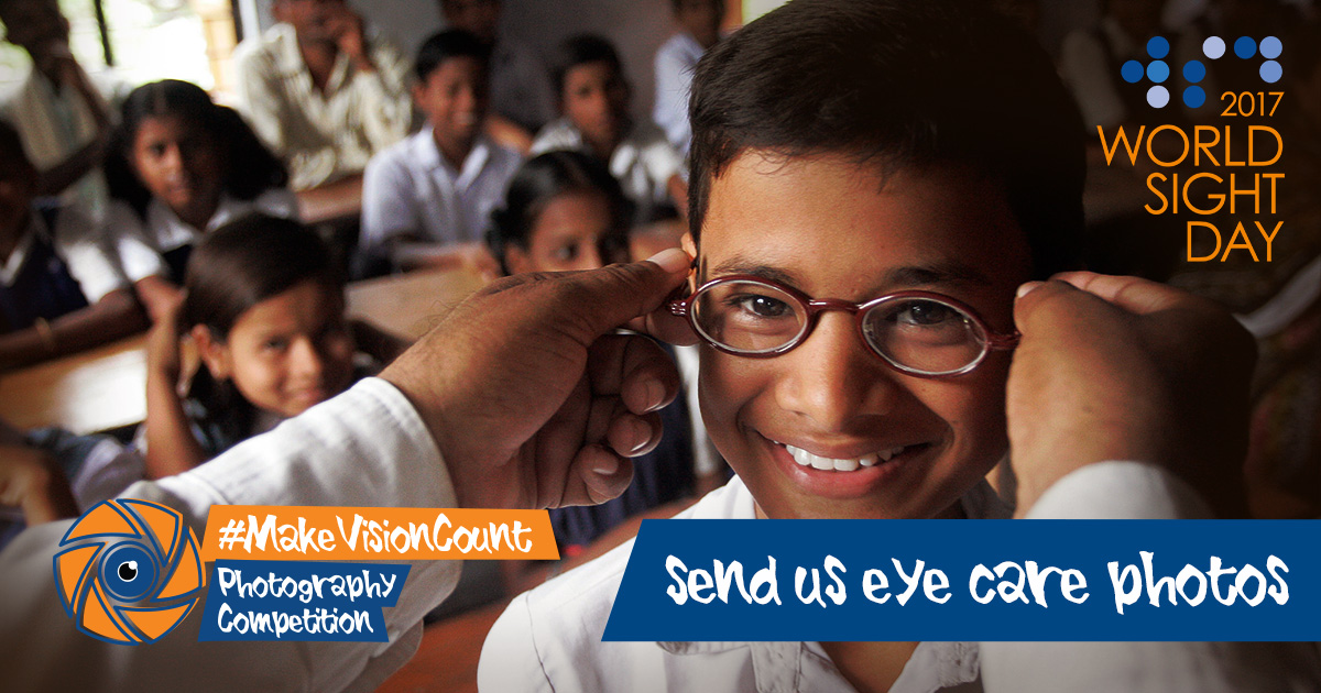 Young boy being given glasses in school while his classmates look on