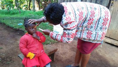 Stella examines a young girl in the community