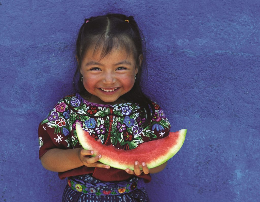 A smiling child holding a half-eaten water-melon